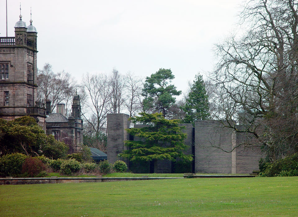 View across lawns. The eventual tonal match of the paving slabs and stone can be seen.